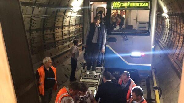 Сотрудники московского метро переводят пассажиров в исправный поезд в тоннеле Солнцевской линии. 21 мая 2019