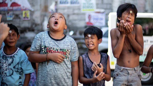 Мальчики играют с монетками во время ежегодного праздника Святой Риты Кашийской в Маниле