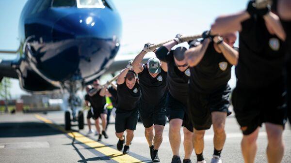 Мужчины тянут самолет JetBlue A320 во время ежегодных соревнований Plane Pull в Международном аэропорту Джона Ф. Кеннеди