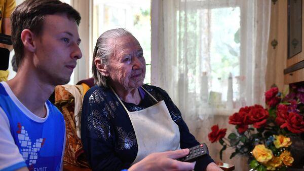 Волонтер помогает в настройке цифровой приставки дома у ветерана Великой Отечественной войны Афросиньи Белозеровой в городе Сочи