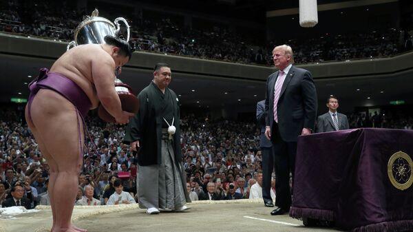 Дональд Трамп вручает кубок президента США победителю летного турнира по сумо в Японии