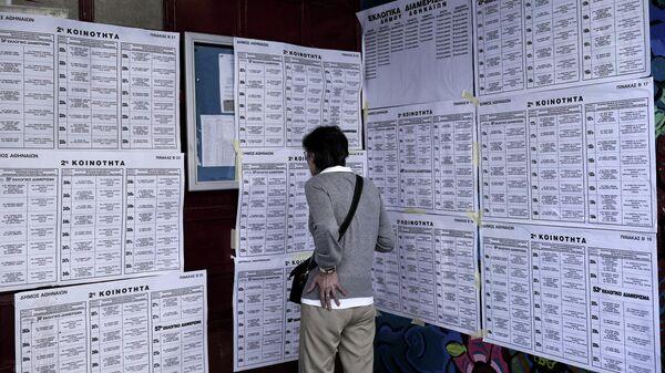 Избиратель знакомится со списками кандидатов в заключительный день голосования на выборах в Европейский парламент на одном их избирательных участков в Афинах. 26 мая 2019