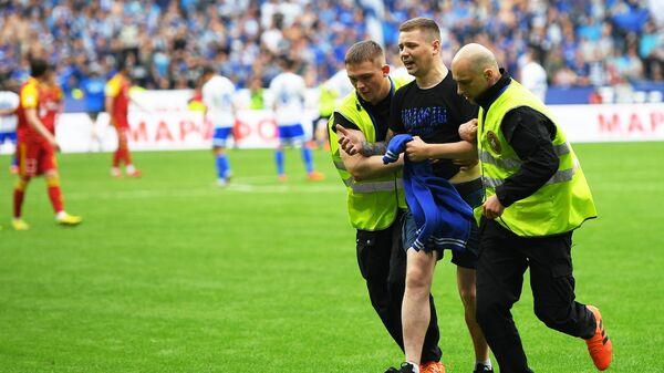 Сотрудники службы охраны уводят с поля болельщика во время матча Динамо - Арсенал
