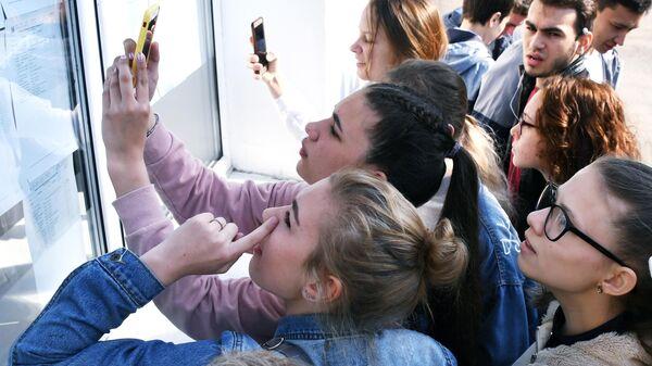 Ученицы ищут свои фамилии в списках на сдачу единого государственного экзамена