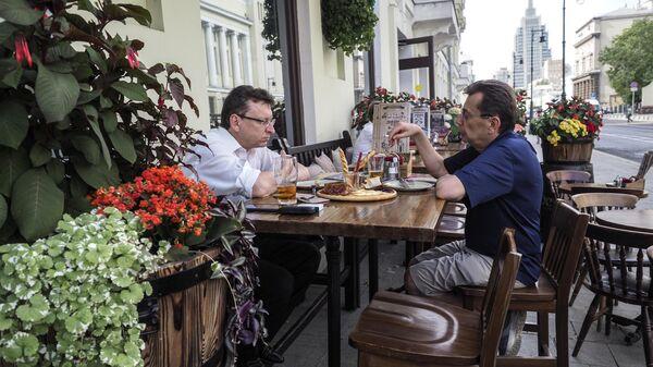 Посетители на летней веранде кафе на улице Малая Дмитровка в Москве