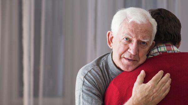 Пожилой мужчина обнимает сына
