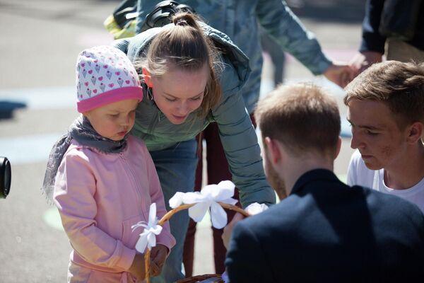 Волонтеры хосписа предлагали прохожим взять белый цветок в обмен на пожертвование для детей с тяжелыми заболеваниями