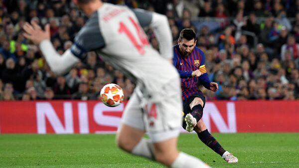 Форвард Барселоны Лионель Месси забивает мяч в ворота Ливерпуля