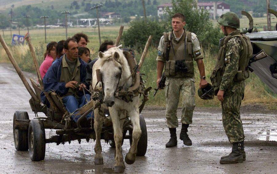 Этнические албанцы проезжают мимо российских военных, дислоцированных у аэропорта Слатина в Приштине