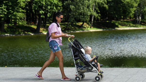 Женщина с ребенком гуляет по набережной пруда в парке Усадьба Михалково