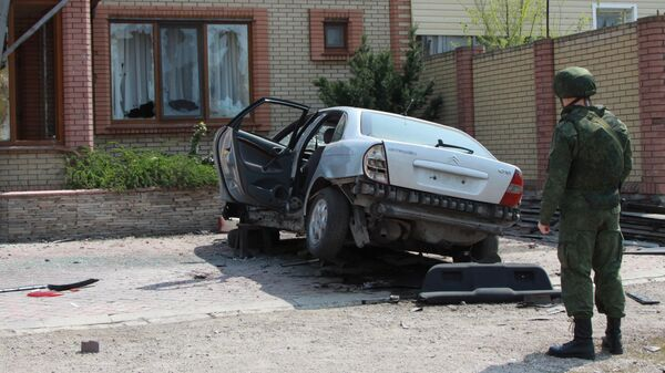 Военнослужащий ДНР у автомобиля, поврежденного в результате артиллерийского обстрела города Докучаевск Донецкой области