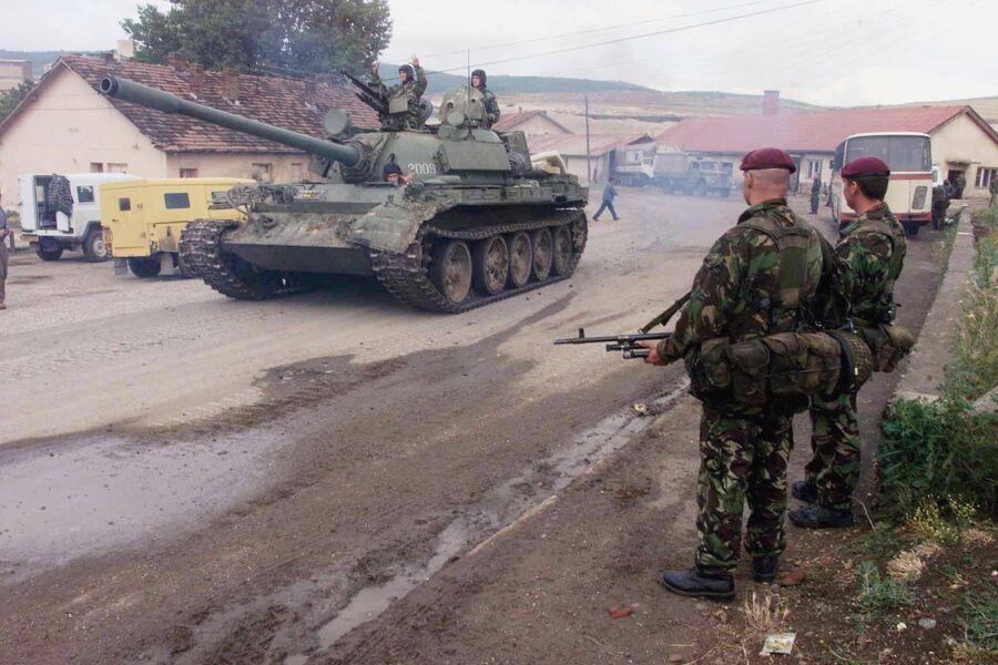 Сербский танк T55 проезжает мимо олдат 1-й воздушно-десантной дивизии Великобритании по дороге к аэропорту Приштины
