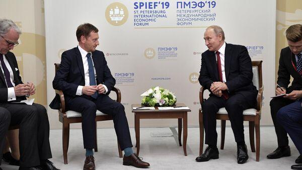 Президент РФ Владимир Путин и премьер-министр федеральной земли Саксония Михаэль Кречмер во время встречи на полях ПМЭФ-2019