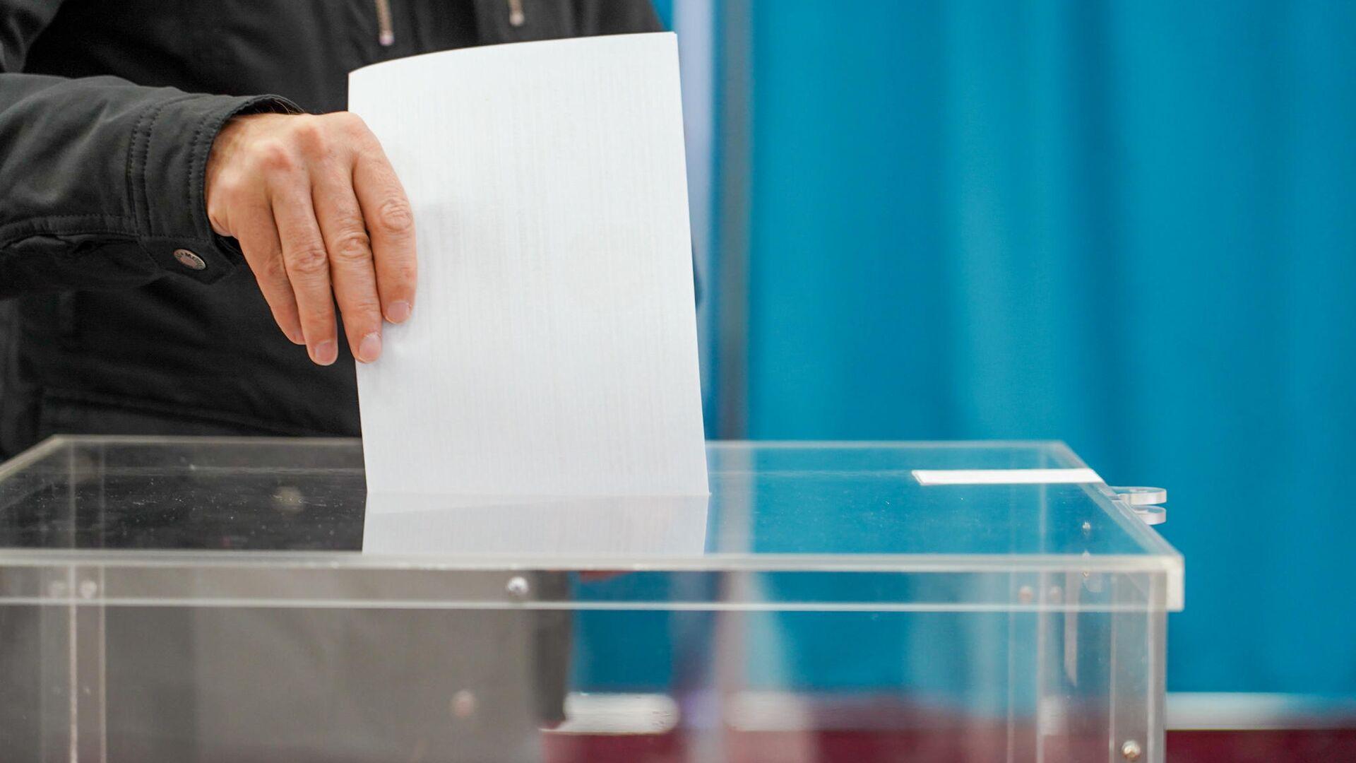 Мужчина опускает бюллетень в урну для голосования - РИА Новости, 1920, 10.01.2021