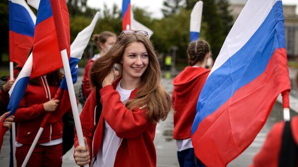 Участники праздничного шествия с флагами России
