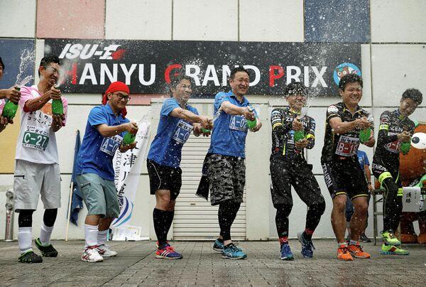 Победители гонки на офисных креслах во время церемонии награждения в Японии