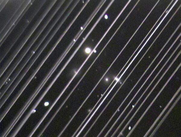 Фотография группы галактик NGC 5353/4 в созвездии Гончих Псов. Светлые линии на снимке – спутники системы Starlink