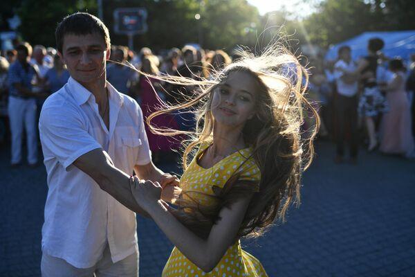 Молодые люди танцуют на общегородском балу на площади Нахимова в Севастополе