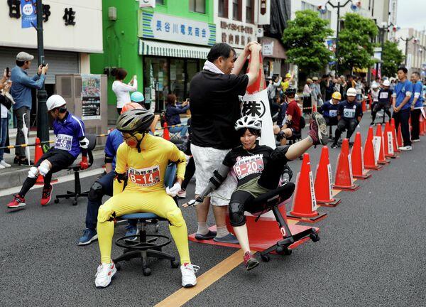 Участники гонок на офисных стульях Ису Гран-При в городе Хань в Японии