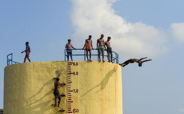 Молодые люди прыгают в реку Буриганга а Дакке, Бангладеш