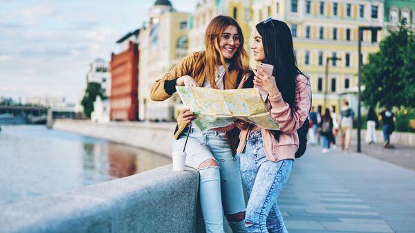 Девушки обсуждают маршрут на набережной