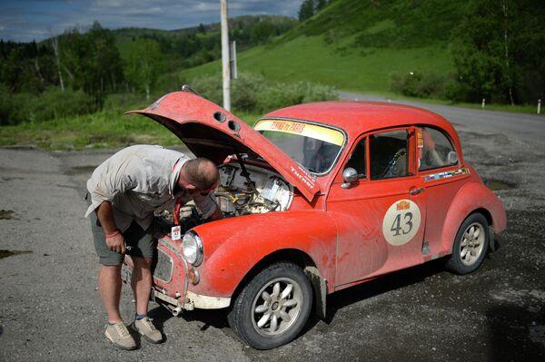 Участник международного ралли на старинных автомобилях Пекин - Париж 2019 на автомобиле Morris Minor (1959 г.) во время технической остановки вблизи села Сугул в Республике Алтай