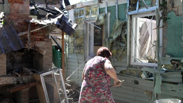Женщина убирает мусор во дворе жилого дома в Донецке, пострадавшего в результате обстрела