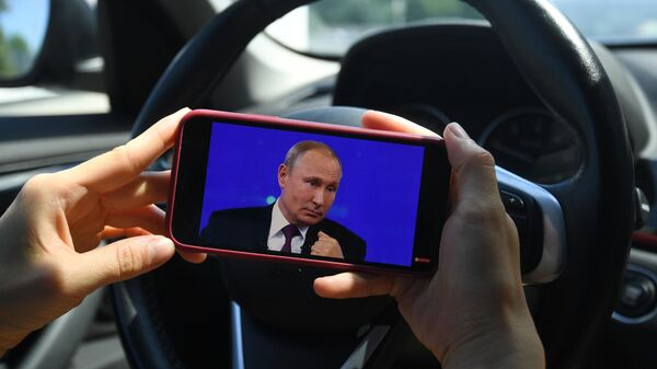 Девушка смотрит трансляцию прямой линии с президентом России Владимиром Путиным