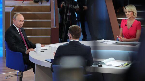 Президент РФ Владимир Путин, корреспондент ВГТРК Павел Зарубин и корреспондент Первого канала Елена Винник во время ежегодной специальной программы Прямая линия с Владимиром Путиным