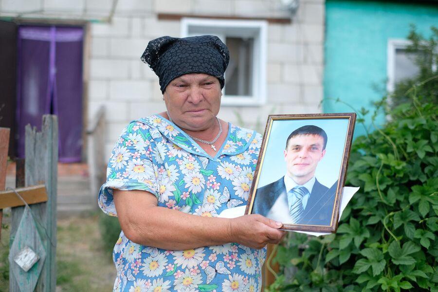 Мать убитого Владимира Грушина держит в руках его фото