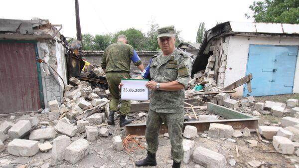 Представители ДНР из Совместного центра по контролю и координации режима прекращения огня в Донбассе фиксируют разрушения от артиллерийских снарядов после обстрела. 25 июня 2019