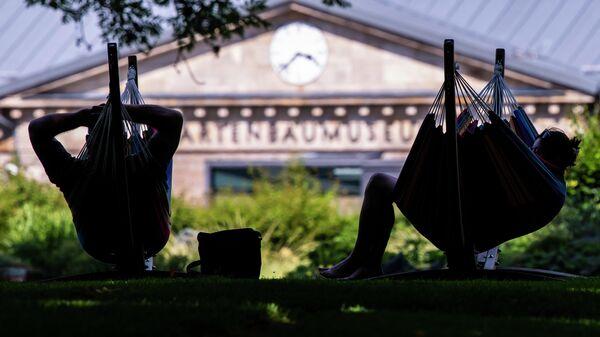 Люди отдыхают в гамаках в Эрфурте, Германия