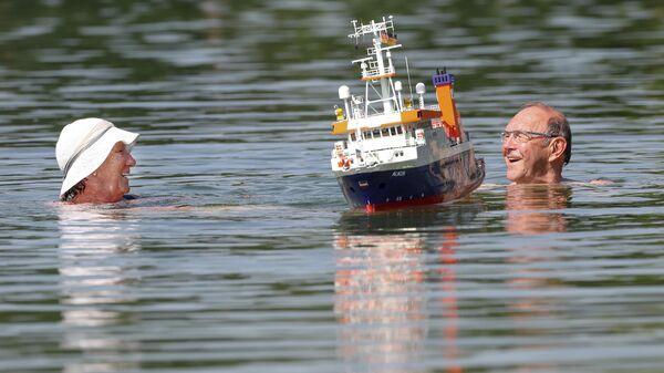 Местные жители купаются в озере во время жары в городе Эртинген, Германия. 26 июня 2019