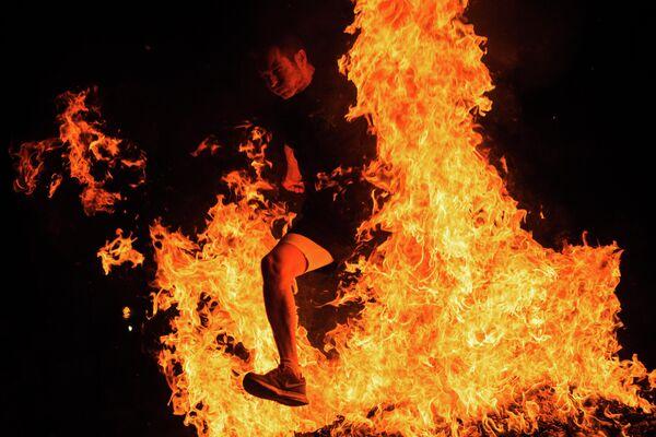 Мужчина прыгает через костер на праздновании Ночи святого Хуана в Испании