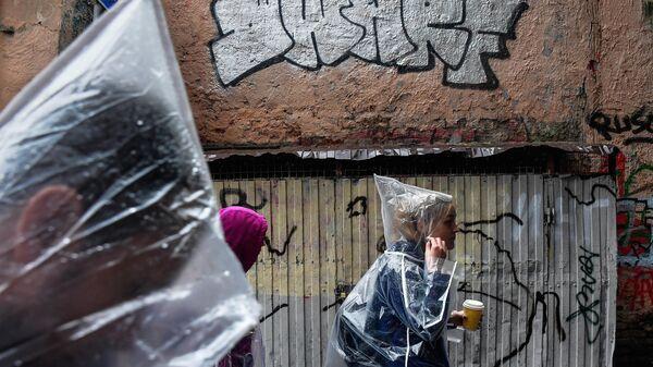 Молодые люди идут мимо граффити-тэга на фасаде дома в Дегтярном переулке