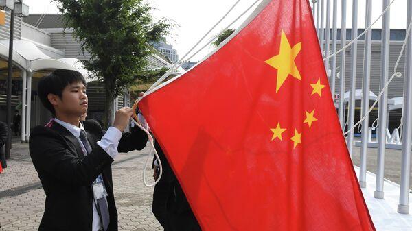 Вывешивание флага Китая перед открытием саммита Группы двадцати в японской Осаке. 28 июня 2019