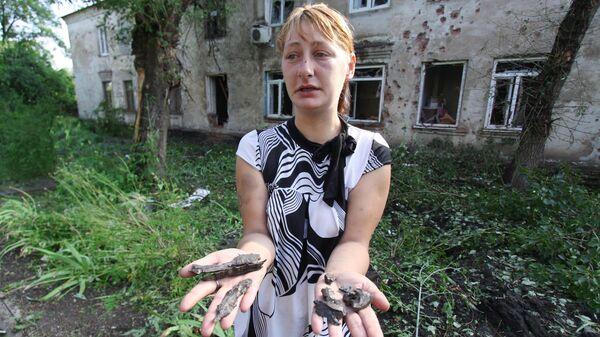 Жительница Донецка с осколками снарядов возле своего дома