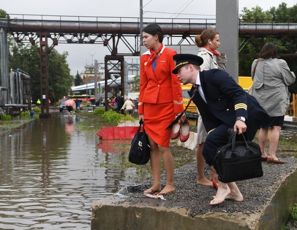 Сотрудники кампании ОАО Аэрофлот- российские авиалинии на затопленной улице в районе аэропорта Шереметьево