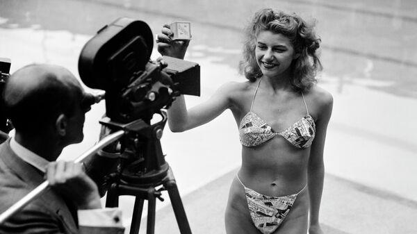Девушка позирует в бикини в бассейне в Париже. 5 июля 1946 года