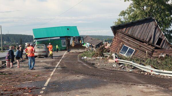 Люди и работники спасательных служб около разрушенных в результате наводнения домов в городе Тулун в Иркутской области