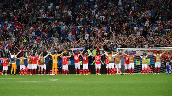 Футболисты сборной России и болельщики приветствуют друг друга