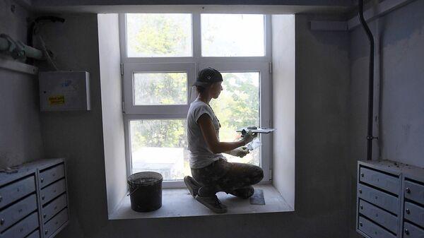 Маляр шпаклюет окно во время ремонта в подъезде жилого дома