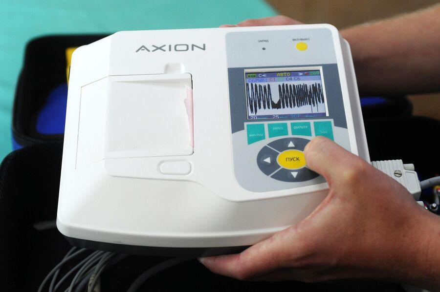Фельдшер станции скорой медицинской помощи проверяет электрокардиограф