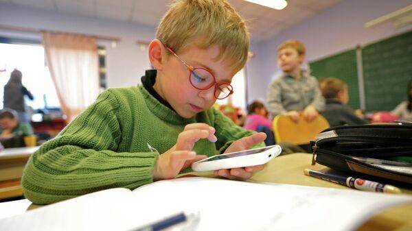 Школьник с телефоном в руках