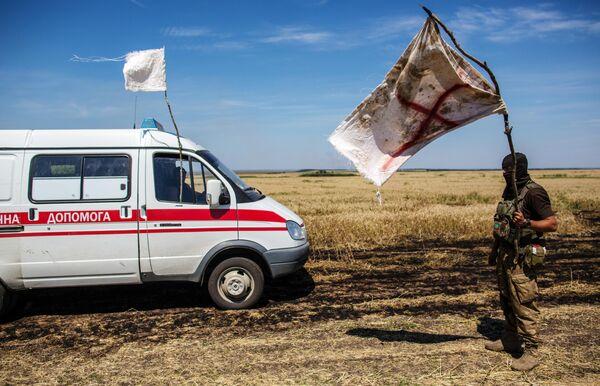 Украинский военный с белым флагом во время передачи убитых на нейтральной территории вблизи поселка Диброво возле российско-украинской границы в Донецкой области