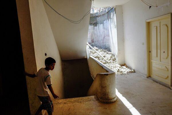 Мальчик из семьи сирийских беженцев в одном из домов в городе Хальба на севере Ливана