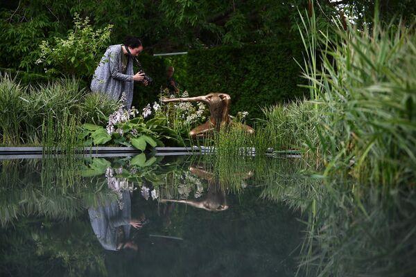 Девушка фотографирует скульптурную композицию на VIII Московском Международном фестивале садов и цветов Moscow Flower Show в парке искусств Музеон