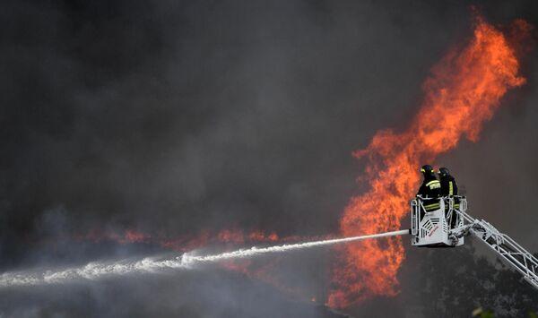 Сотрудники противопожарной службы МЧС РФ во время тушения пожара в здании около Северной ТЭЦ в Мытищах