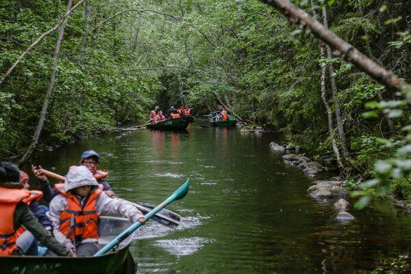 Туристы плывут на лодке вдоль рукотворных каналов между озерами на Соловецких островах