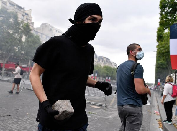 Участник беспорядков на Елисейских полях в Париже. 14 июля 2019